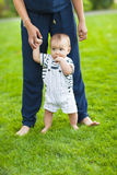 Baby learning to walk outdoors. Happy mother and her son playing Royalty Free Stock Photo