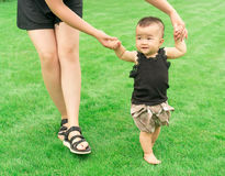 Baby learning walking. Green bg Stock Image