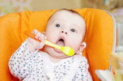 Baby learns to eat with spoon Stock Images