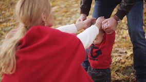 The baby learns to walk. Mom and Dad help his son to take the first steps stock video footage