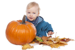 Baby with leaves and a pumpkin Royalty Free Stock Photos