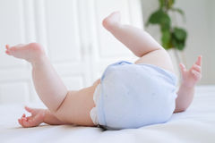 Baby legs and bottom in diaper and blue body suit Royalty Free Stock Images