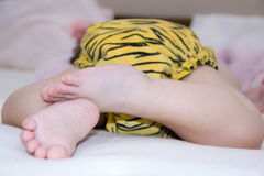 Baby legs and bottom in leopard coloring diaper in bed Stock Photos