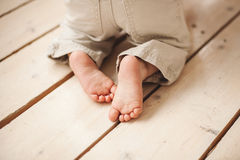 Baby legs in pants on wooden floor Stock Photos