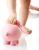 Baby legs on piggy bank royalty free stock photography