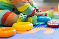 Baby legs sitting on a colourful carpet with many coloured pijamas Royalty Free Stock Photo