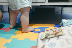 Baby legs standing up on a play game ground Stock Images