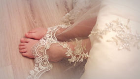 Baby legs from under the lace dress. Tender feet girls look out from under a beautiful vintage lace dresses Stock Image