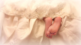 Baby legs from under the lace dress. Tender feet girls look out from under a beautiful vintage lace dresses Royalty Free Stock Photo