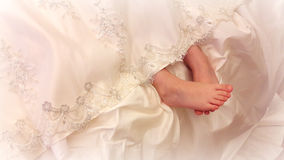 Baby legs from under the lace dress. Tender feet girls look out from under a beautiful vintage lace dresses Stock Photos