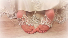Baby legs from under the lace dress. Tender feet girls look out from under a beautiful vintage lace dresses Stock Images