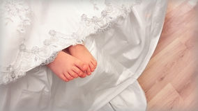 Baby legs from under the lace dress. Tender feet girls look out from under a beautiful vintage lace dresses Royalty Free Stock Image