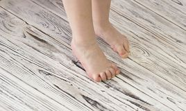 Baby legs on a white wooden background learning royalty free stock images