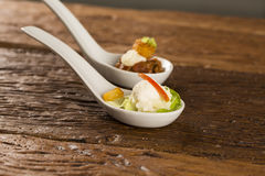 Baby lettuce salad, cherry tomatoes, palm hearts, cauliflower sauce, fried manioc and salted whipped cream in a spoon. Stock Photography
