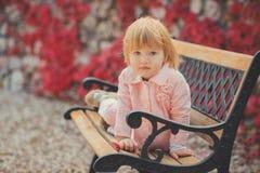 Baby leuk meisje die met blond haar en roze appelwang de tijdvakantie van de de lenteherfst van het stellen in mooi tuinhoogtepun stock fotografie