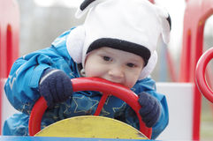Baby licks auto rudder on playground Royalty Free Stock Photos