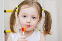 Little girl licks sweet lollipop. Little girl licks sweet orange round lollipop royalty free stock photos