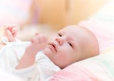 Baby lie in cradle and look forward. Newborn baby lie in cradle stock photo