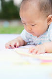 Baby lie prone on ground at park. Cute Asian baby lie prone on ground at park Royalty Free Stock Images