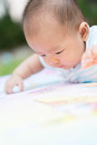 Baby lie prone on ground at park. Cute Asian baby lie prone on ground at park Stock Image