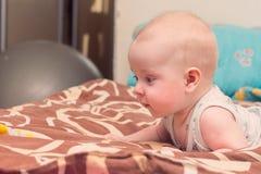 Baby liegt auf Bett auf seinem Magen Lizenzfreies Stockfoto