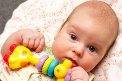 Baby liegt mit Spielzeug Stockbilder