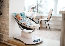 Baby lies in an automatic carrycot in the light room stock photos