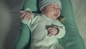 Baby lies on bed and crying. Mom gives him a dummy and strokes his cheeks. stock footage