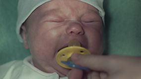 Baby lies on bed and crying. Mom gives him a dummy and strokes his cheeks. Kid calms down. Close up stock video footage