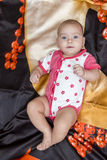 Baby lies on bedding. Serious baby in white and pink dress lying on the dark bedding on back Stock Photo