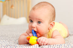 Baby lies and gnaws  toy Stock Images