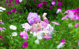 The baby lies on the grass in flowers Royalty Free Stock Image