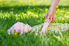 Baby lies on grass in park, mother hand touches his hand Stock Photo