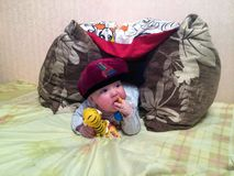 The baby lies in a makeshift tent. Boy playing with toys Stock Photos
