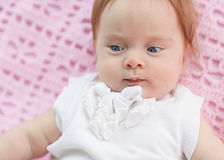 The baby lies on a pink towel. She's in pink shorts and a white blouse Royalty Free Stock Image