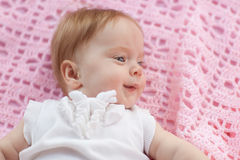 The baby lies on a pink towel. She's in pink shorts and a white blouse Stock Images