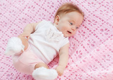 The baby lies on a pink towel. She's in pink shorts and a white blouse Stock Photos