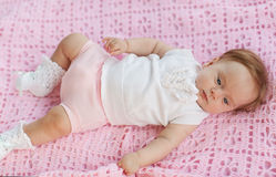The baby lies on a pink towel. She's in pink shorts and a white blouse Stock Photo