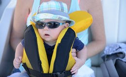 Baby with lifejacket on that needs to be zipped up with sunglass. Mother holding baby with lifejacket on that needs to be zipped up with sunglasses and hat Royalty Free Stock Photo