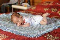 Baby ligger på hans mage arkivfoto