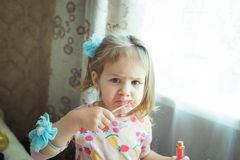 Baby with lipstick. Portrait of little girl with lipstick Stock Image
