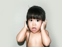Baby listen music from headphone Stock Photos