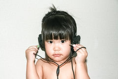 Baby listen music from headphone Royalty Free Stock Photos