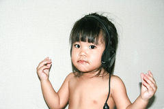 Baby listen music from headphone Stock Photo