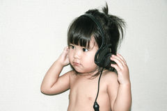 Baby listen music from headphone Stock Images