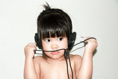 Baby listen music from headphone Royalty Free Stock Image