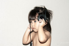 Baby listen music from headphone Royalty Free Stock Photography