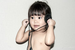 Baby listen music from headphone Royalty Free Stock Images