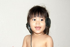Baby listen music from headphone portrait Stock Image