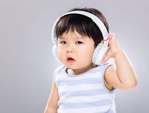 Baby listen to music stock image